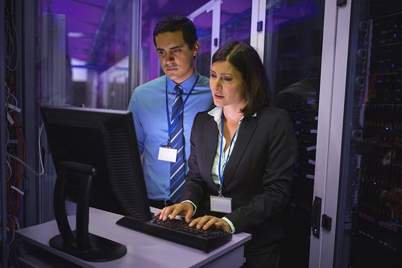 Two people stood in a data centre, looking at big data analytics