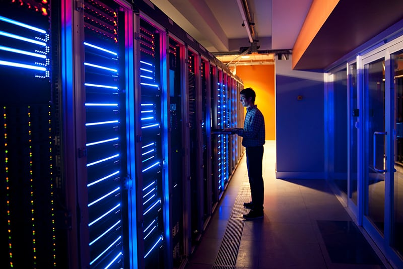 A man stood in a data centre, managing a company's virtual infrastructure